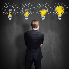 successful businessman standing in front of a blackboard with lightbulbs, symbolizing having an...