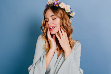 Wall Mural - Chilling european girl in flower wreath posing on blue background. Indoor portrait of good-looking lady touching her face with eyes closed.