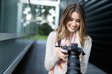 Woman is a professional photographer with dslr camera Fotobehang