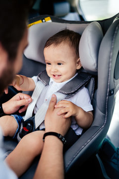 Smiling baby in child car seat going for a family roadtrip. Safety seatbelt