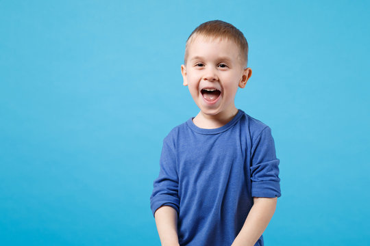 Smiling overjoyed excited happy fun kid boy 4 years old wearing blue t-shirt clothes isolated on blue wall background children studio portrait. People childhood lifestyle concept. Mock up copy space.