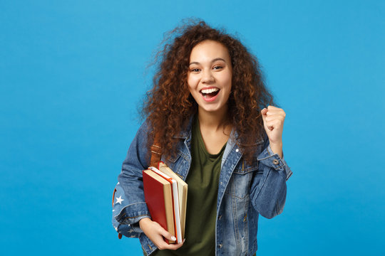 Young african american girl teen student in denim clothes, backpack hold books isolated on blue wall background studio portrait. Education in high school university college concept. Mock up copy space