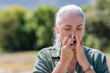 Woman using nasal spray for allergy