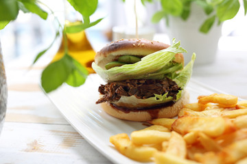 Burger with chopped beef. Tasty bread roll served with roasted French fries.