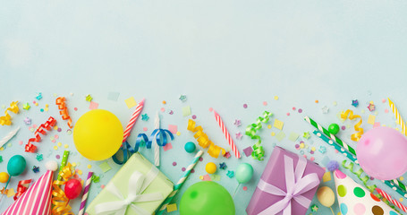 Holiday background with balloons, gift boxes and confetti. Birthday and party supplies on blue...