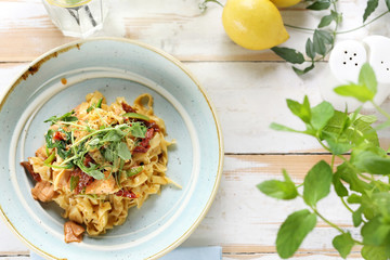 Tagliatelle with salmon and sun-dried tomatoes. Appetizing dish. Top view