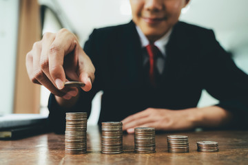 Businessman putting coin stack step up increase save money.