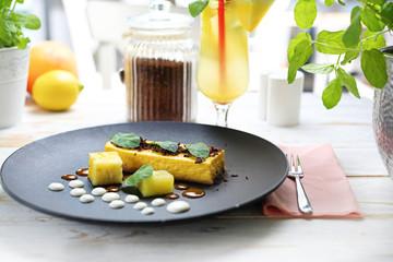 Cake. Delicate mango cheesecake with chocolate sauce