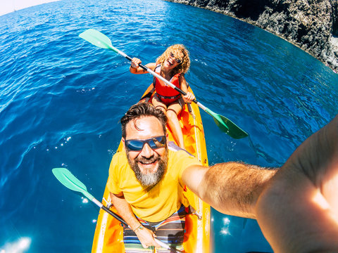 Selfie couple with top vertical point of view - happy active adult people enjoy kayak at the ocean - summer tourist in holiday vacation lifestyle - action camera and cheerful man and woman