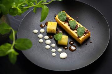 Sweet dessert. Mango cheesecake with chocolate sauce.