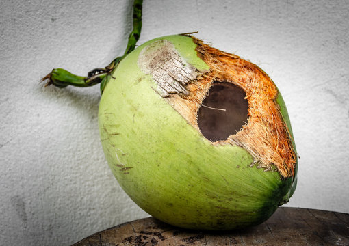 Green coconut with hole on table
