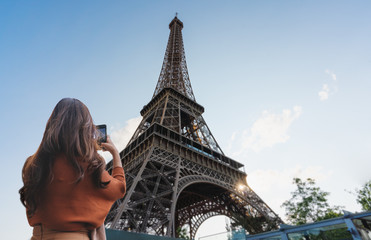 Wall Mural - Travelling in Europe, Traveler woman taking photo of Eiffel Tower, famous landmark and travel destination in Paris, France by mobile smartphone