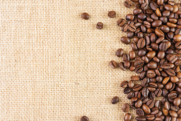 Coffee beans on a background of burlap. Place for text. Concept of making coffee, coffees.