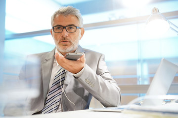 Businessman talking on cellphone with headphones in contemporary office