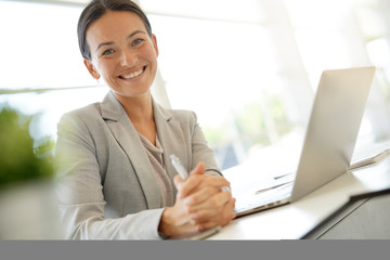 Smiling young businesswoman at desk looking at camera