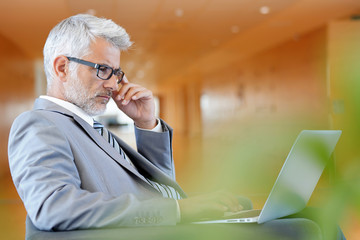 Serious businessman concentrating on laptop in reception area