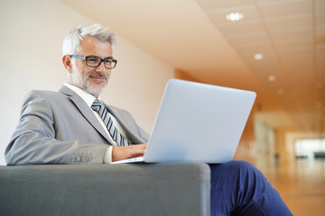 Cheerful businessman looking at laptop in lounge area