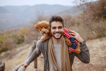 Handsome bearded mixed race man dressed casual walking in nature at fall and carrying his apricot poodle on shoulders. Fototapete