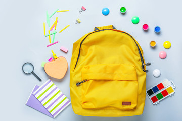 Backpack with school supplies on grey background