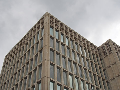 a corner detail of a typical brutalist style 1960s concrete office building with geometric concrete framework against a grey cloudy sky