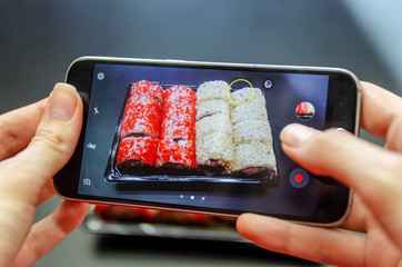 A girl photographs red and white sushi on the phone from different angles. Photo close up.