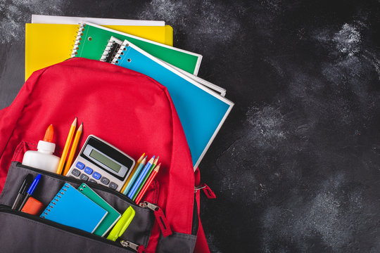 Backpack With School Supplies on a Blackboard Background