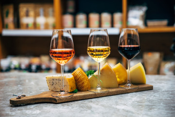 Glasses of Wine and cheese. Assortment or various type of cheese and wine glasses on the table in restaurant. Red, rose and yellow wine or champagne on the table. Winery concept image