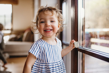 A toddler girl standing by window indoors at home, looking at camera. Fotoväggar