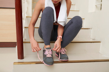 Young woman sitting on steps and tying shoe laces of sneakers