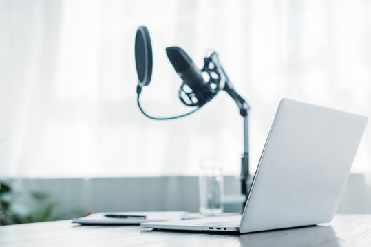 selective focus of laptop near microphone on desk in broadcasting studio