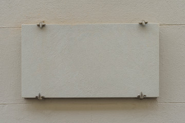A blank stone plaque sign on a wall in Italy.