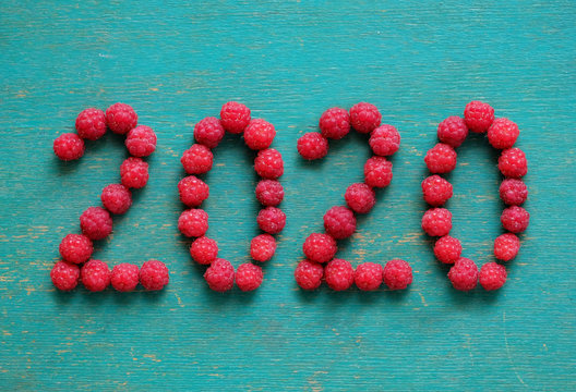 happy new year 2020 made of berries on a blue wooden background