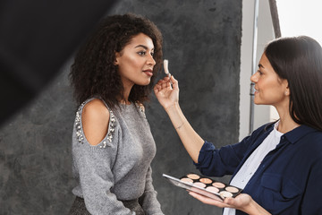 Portrait of female makeup artist applying professional cosmetics to pleased woman during photo shooting in studio