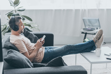 adult man in earphones sitting on sofa with legs on table and using smartphone