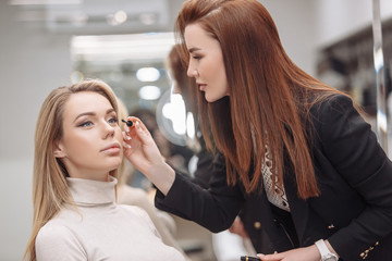 Red-haired woman make-up artist applies make-up of beautiful young blonde girl to client sitting in beauty salon chair. Concept creating bright and beautiful image for graduation and corporate parties