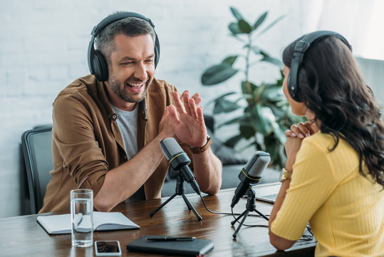 cheerful radio host showing no sign while recording podcast with colleague