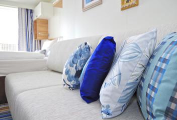Nahaufname Couch mit gemusterten Kissen in Kabine auf Kreuzfahrtschiff von TUI Cruises