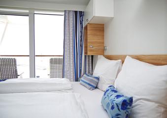 Doppelbett mit Dekokissen vor Schiebetür in Balkonkabine auf Kreuzfahrtschiff von TUI Cruises