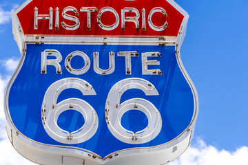 Fotorolgordijn Route 66 Red, white and blue neon sign on the famous, historic Route 66 in front of blue sky