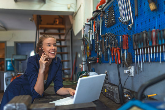 Business woman at a factory. Craftswoman working using a laptop in the garage. Mechanic using laptop at the repair garage. Young female mechanic with laptop. Business woman at a factory.