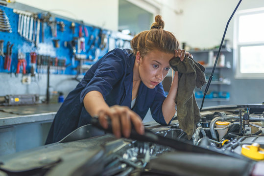 Portrait of smiling young female mechanic inspecting a CV joing on a car in auto repair shop. Mechanic smiling at the camera at the repair garage. Proud Female Mechanic.