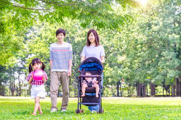 新緑の樹木をバックに公園を散歩する4人家族。育児、愛情、幸せイメージ