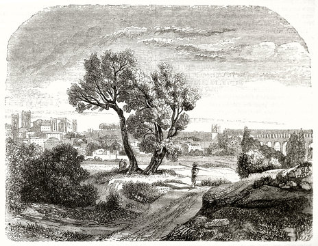 Ancient path crossing the nature in a landscape context with an ancient city far on background. Old  view of Montpellier France. Grayscale etching style illustration on Magasin Pittoresque Paris 1848