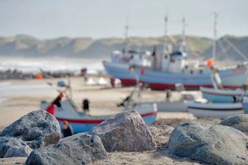 Dänische Nordseeküste - Steine im Fordergrund, Hintergrund mit Schiffen unscharf