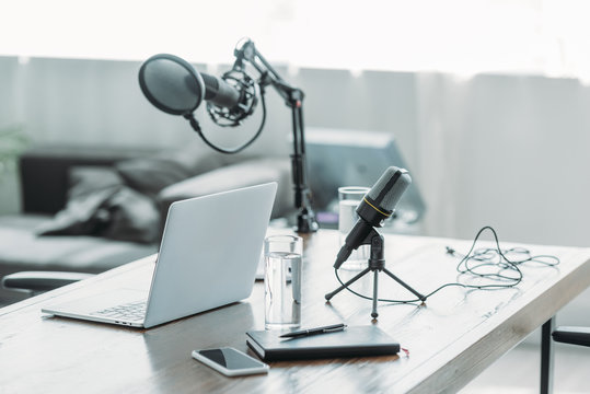 wooden desk with microphone, laptop, smartphone, notebook and glasses of water in broadcasting studio