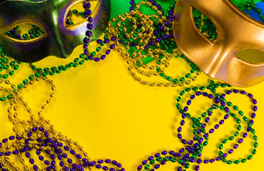 Wall Mural - Two Mardi Gras mask with colorful beads on a yellow background