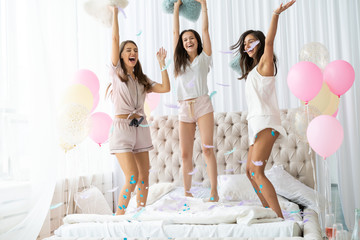 Yeah! Four attractive young women in pajamas smiling and gesturing while jumping in the bedroom...
