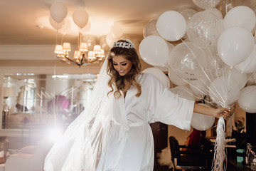 Pretty Young Bride Model Holding Bunch of Balloons. Woman Wearing Gown, Looking Down and Keeping in Hand Helium Air Bubbles. Colorful Photo of Wedding Day. Hotel Apartment Interior on Background
