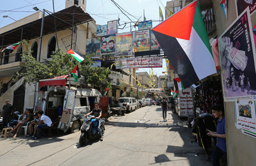 A boy rides on a motorbike as he drives past Palestinian flags at Burj al-Barajneh refugee camp in Beirut