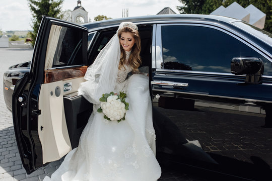 Beautiful Bride with Flower Bouquet in Limousine. Pretty Young Woman Wearing White Wedding Dress and Tiara with Veil. Girl Holding in Hand Roses Bunch and Sitting in Black Limo Car. Outside Photo